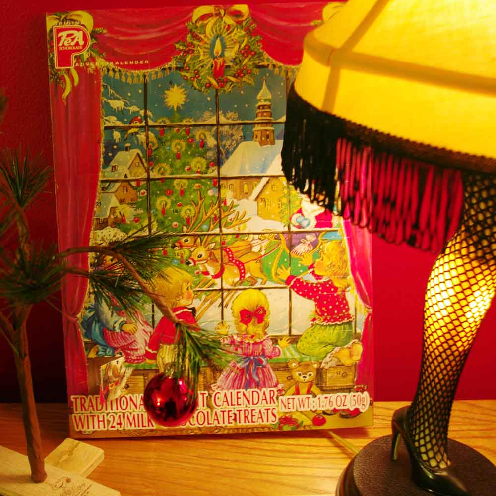 "A cardboard advent calendar behind a leg lamp from ""A Christmas Story"" next to a sad little spindly tree from ""A Charlie Brown Christmas."""