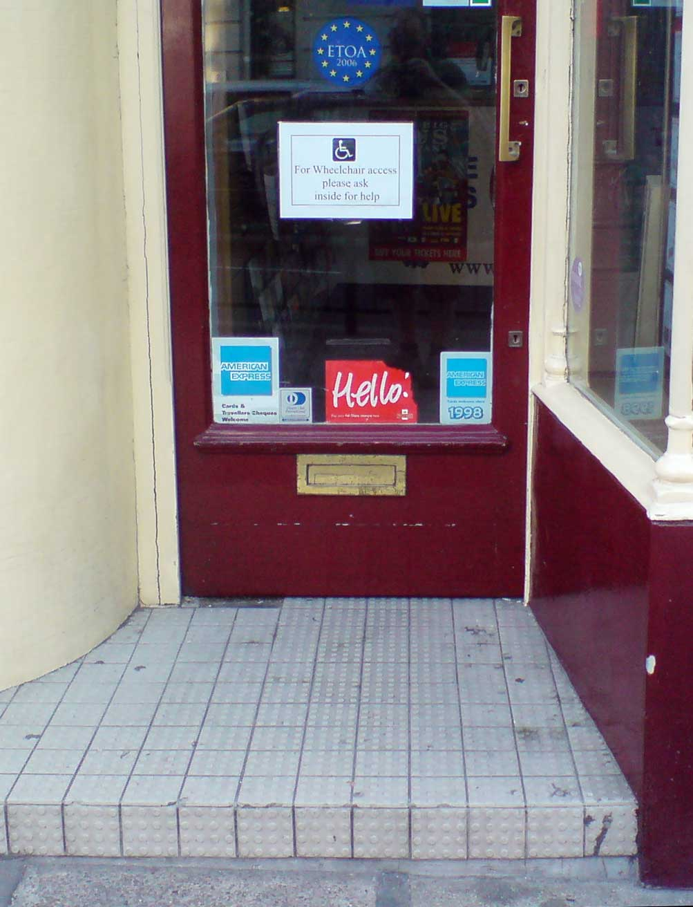 "Door with a sign, ""For Wheelchair access please ask inside for help."" In front of the door is a roughly 4-inch high step. Image by Darren Foreman."