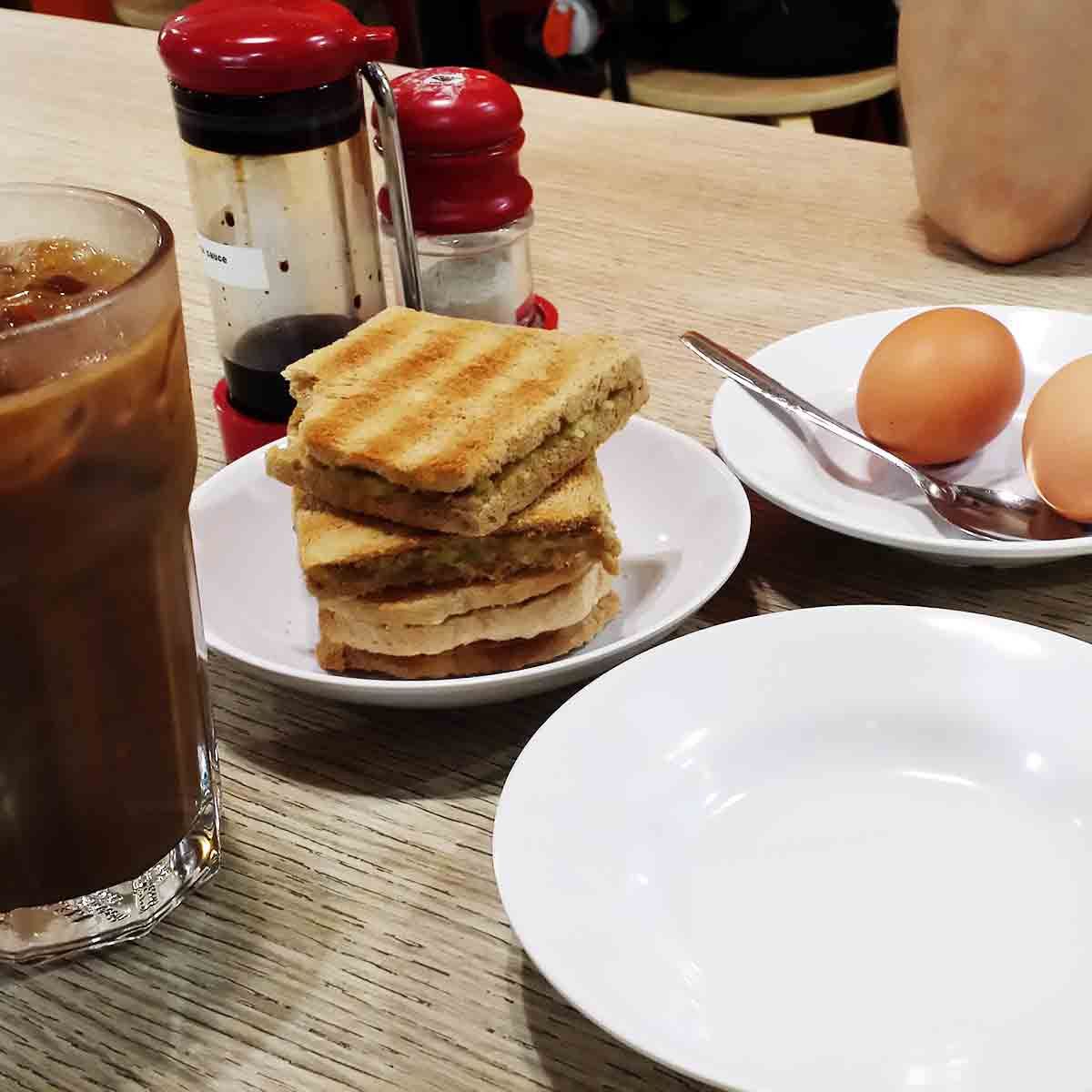 Glass of iced coffee, a stack of squares of kaya toast, a plate with soft-boiled eggs in the shell, a caddy with white pepper and soy sauce containers.