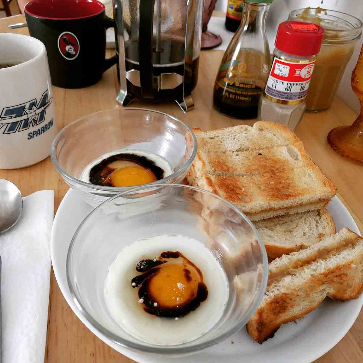 One poached egg each in two custard cups, with a bit of soy and white pepper. The cups are on a plate alongside a stack of kaya toast (kaya and butter sandwiched between toast cut into strips). In the background is a coffee mug next to a French press, along with the condiments used in the breakfast.