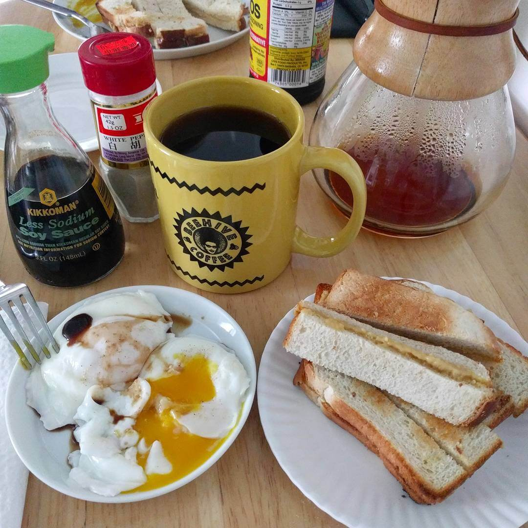 Poached eggs in a saucer with soy sauce and white pepper, one egg is broken so the yolk is flowing. Another plate with strips of kaya toast (toasted country white with kaya jam between slices, cut into strips). A yellow coffee mug with the Beehive Coffee logo full of coffee. A Chemex, some low-sodium soy sauce, and white pepper are visible in the background.