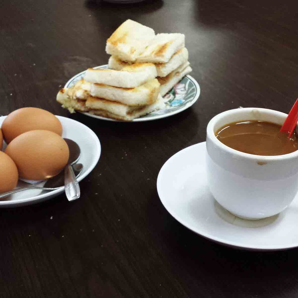 A plat of kaya toast strips, a plate with five soft-boiled eggs, a saucer and cup with coffee and cream and an odd red plastic spoon.
