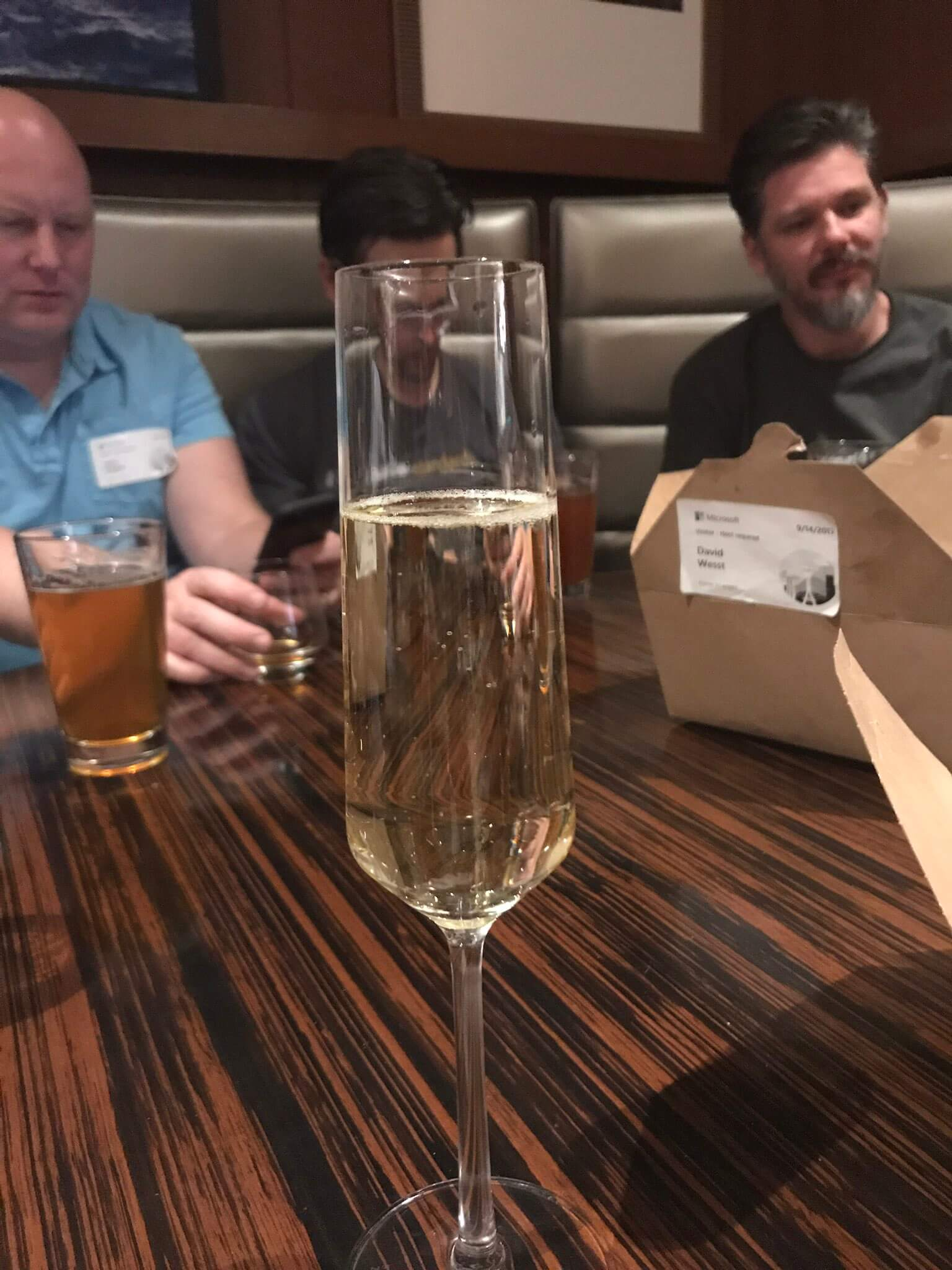 A mostly full Champagne flute in the foreground, a cardboard takeaway container behind it, and blurry people sitting in a booth in the background.