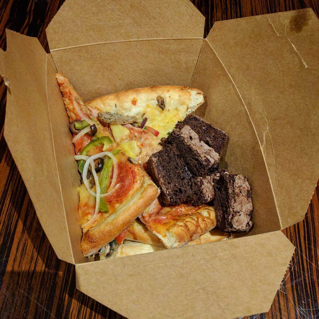 An opened cardboard takeaway container filled to the top with thin slices of pizza and a pile of brownies.
