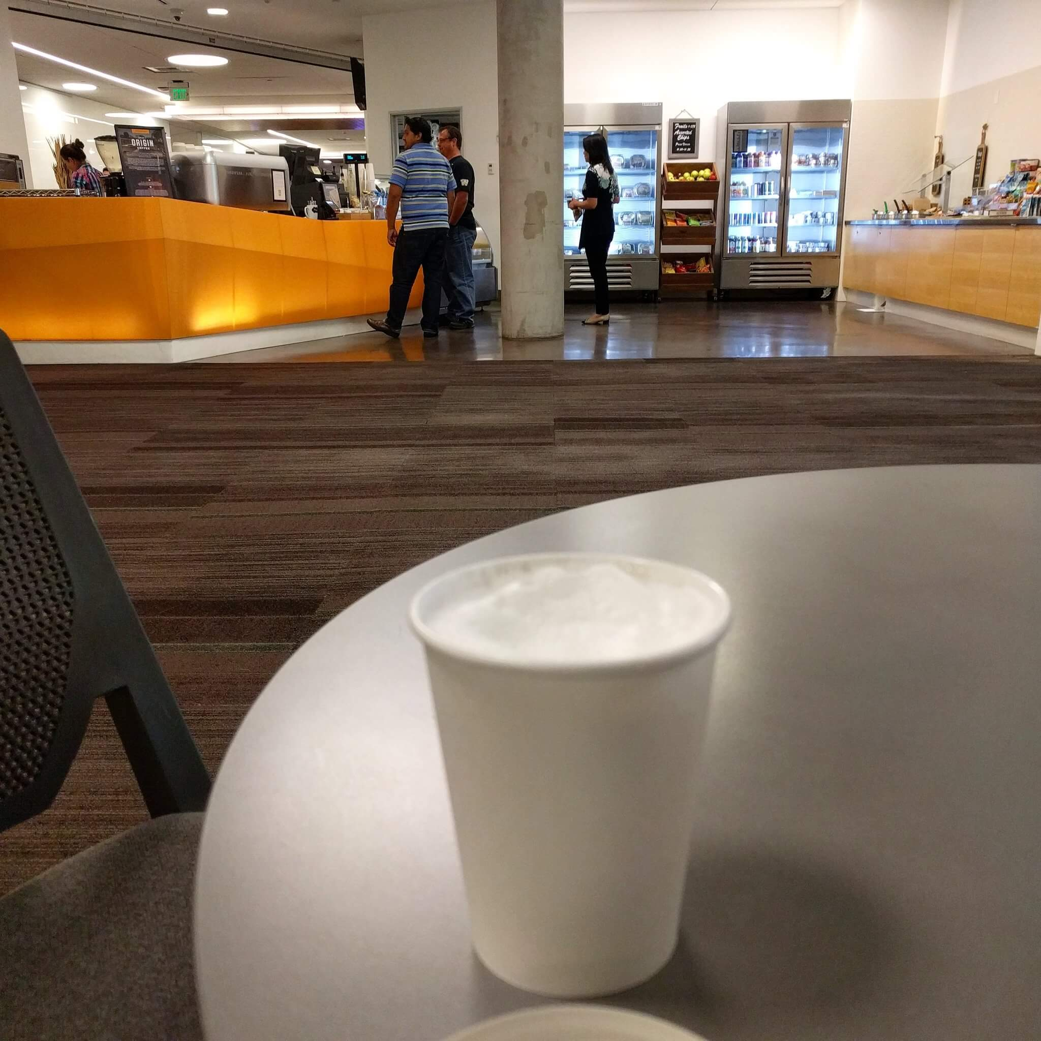 Cappuccino in a paper cup in the foreground, coffee bar and drink cases in the far background, a gulf of carpet between us.