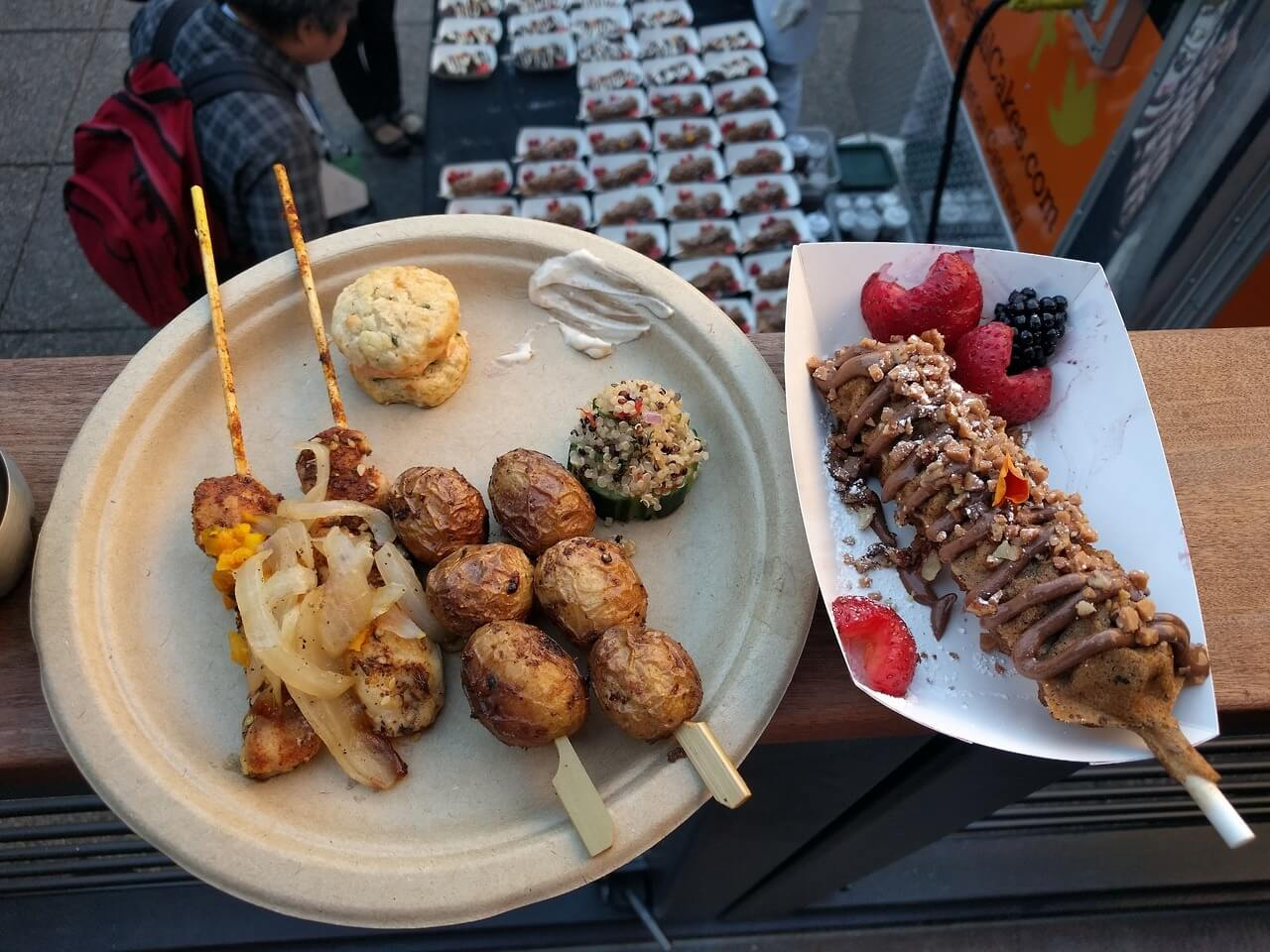 View of my dinner plate with chicken skewers, salt potato skewers, and other snacks, alongside a dessert treat on a stick.