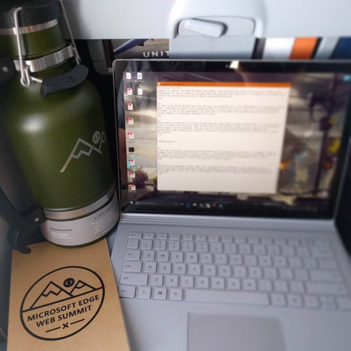 My laptop on the airplane tray table along with the free 'Microsoft Edge Web Summit' branded Moleskine. Crowding them both off the tray a bit and jammed up against the bulkhead is the giant insulated 64oz drink container, also emblazoned with 'Microsoft Edge Web Summit'.