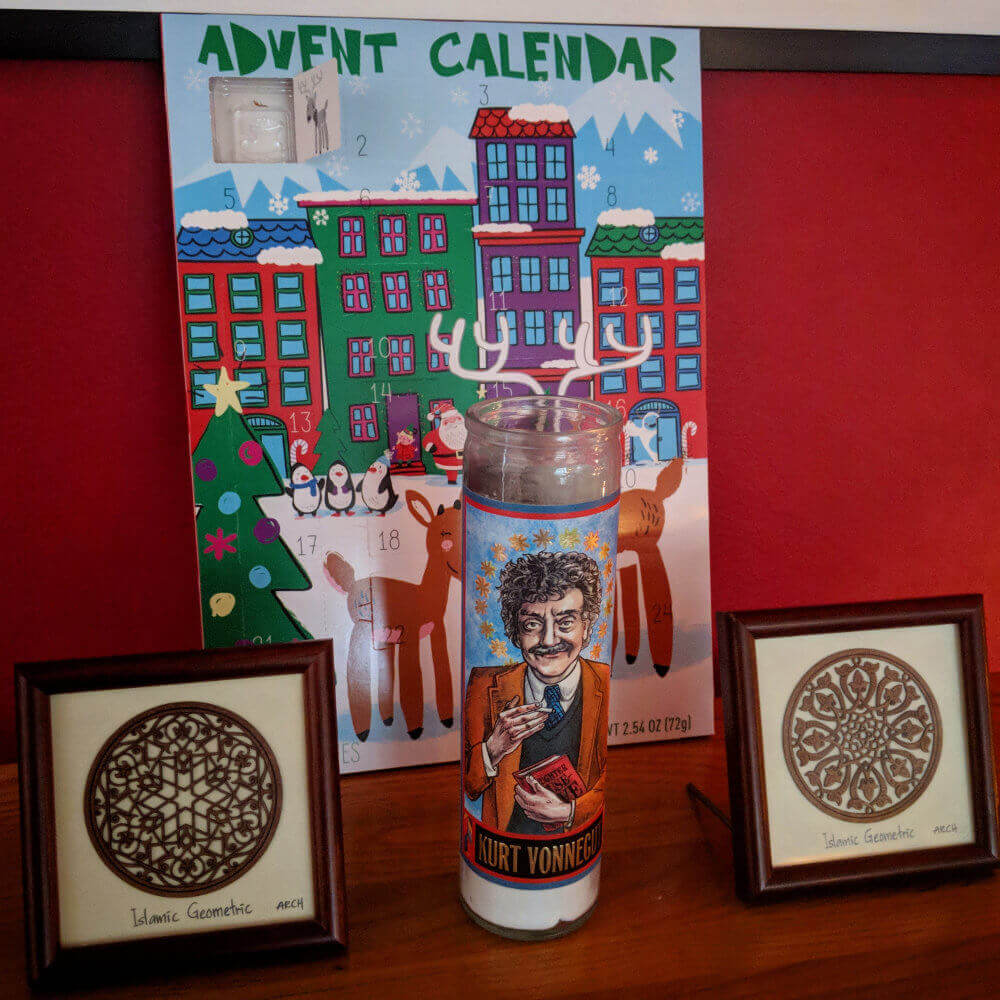 A cardboard advent calendar behind a Kurt Vonnegut saint candle and two framed Islamic geometric design prints.