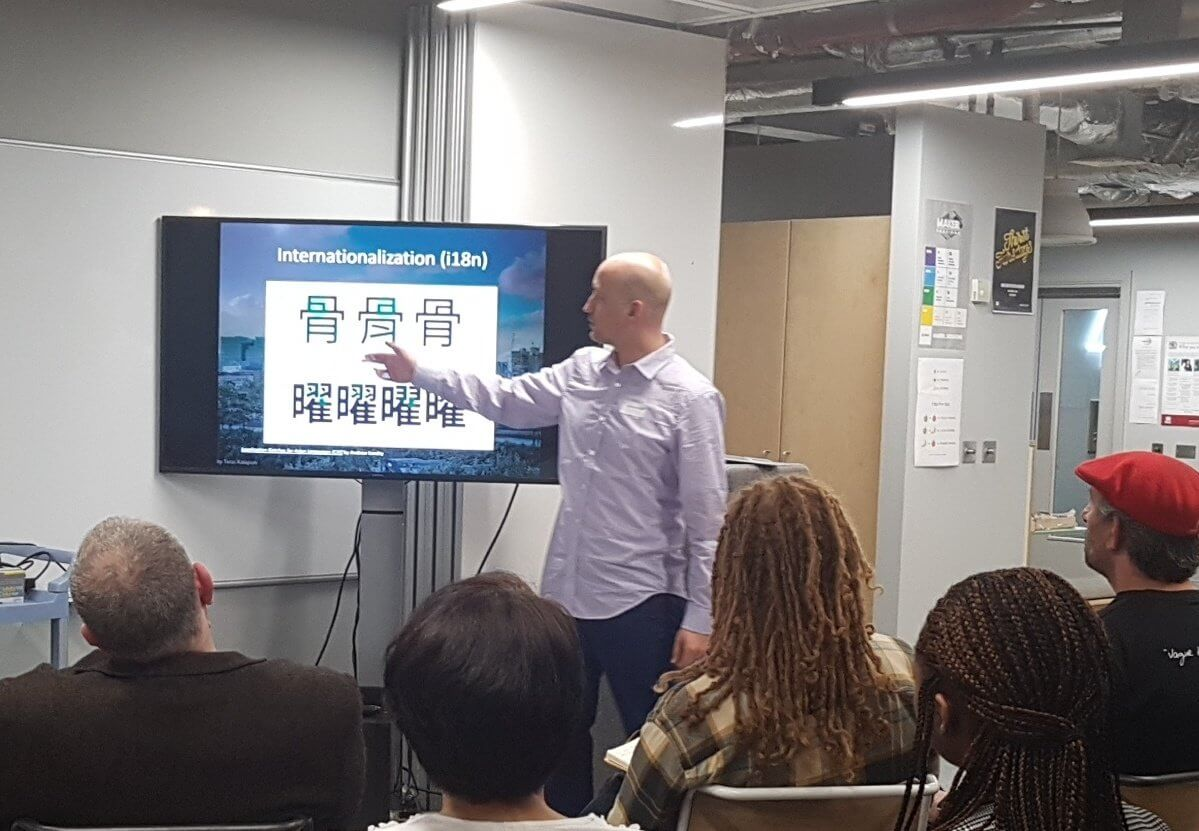 Adrian pointing at a slide showing subtle rendering differences of the same Chinese character, depending on which language it is being rendered for.