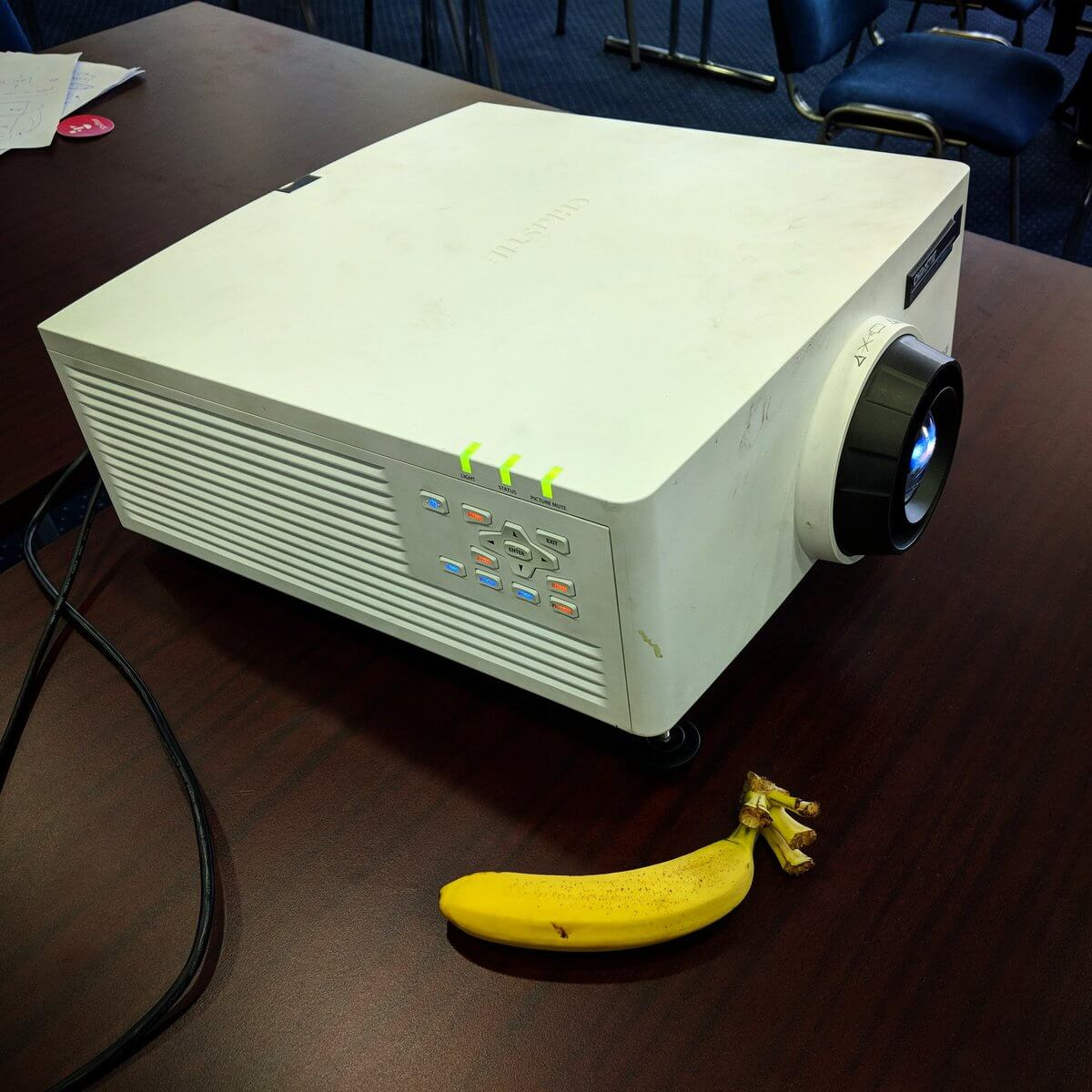 A large computer projector with a worn cover.  It is about a foot-and-a-half square and two-thirds as tall. It has a bank of status lights on one side. Beside it is a banana, dwarfed by the projector.