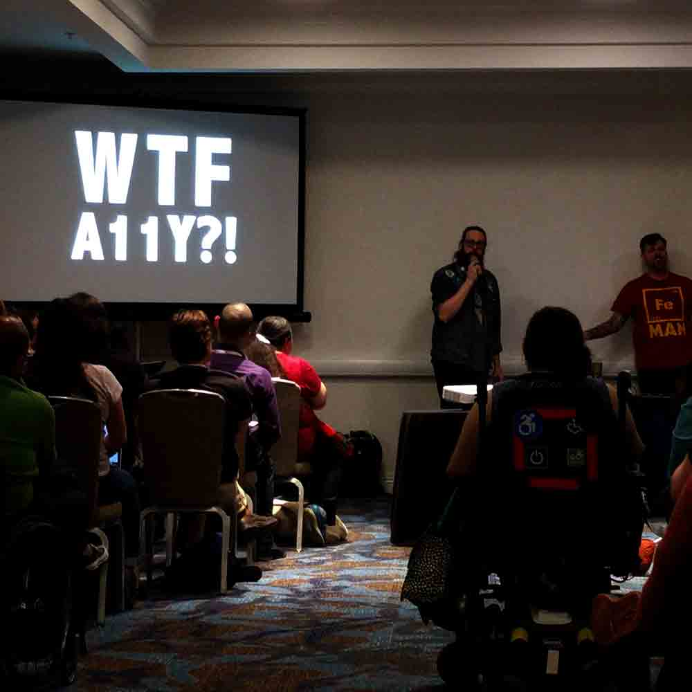 "Billy Gregory and Karl Groves standing in front of a project slide that reads ""WTF A11y?"""