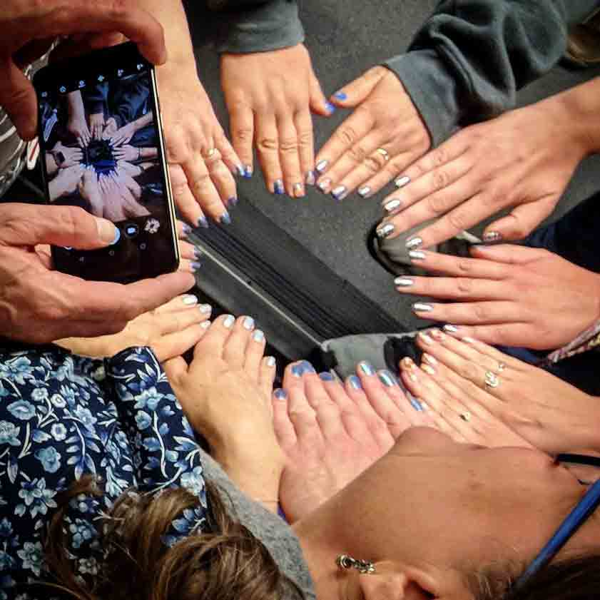 A circle of 12 hands all showing their nails to Bruce's cell phone camera.