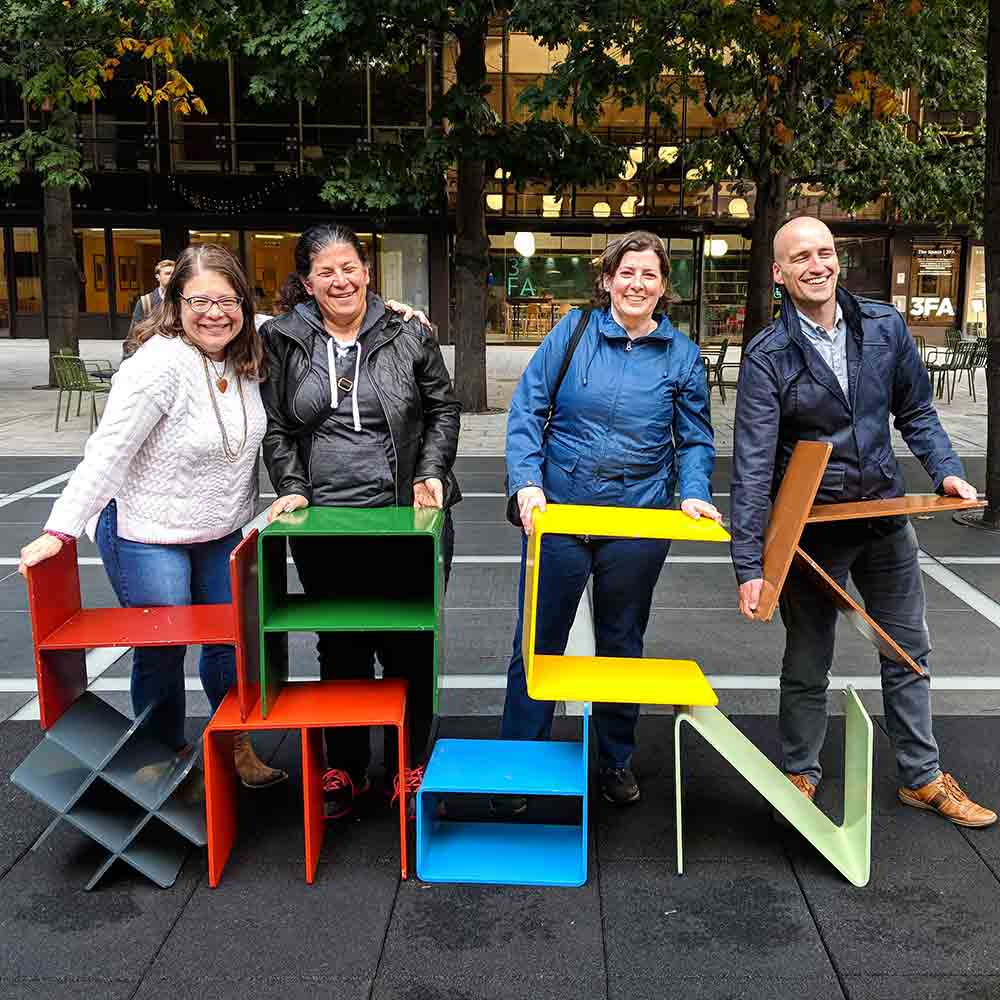 Glenda, Estelle, Janet, and Adrian holding colorful metal letters to spell 'hack' and '#mdn'.