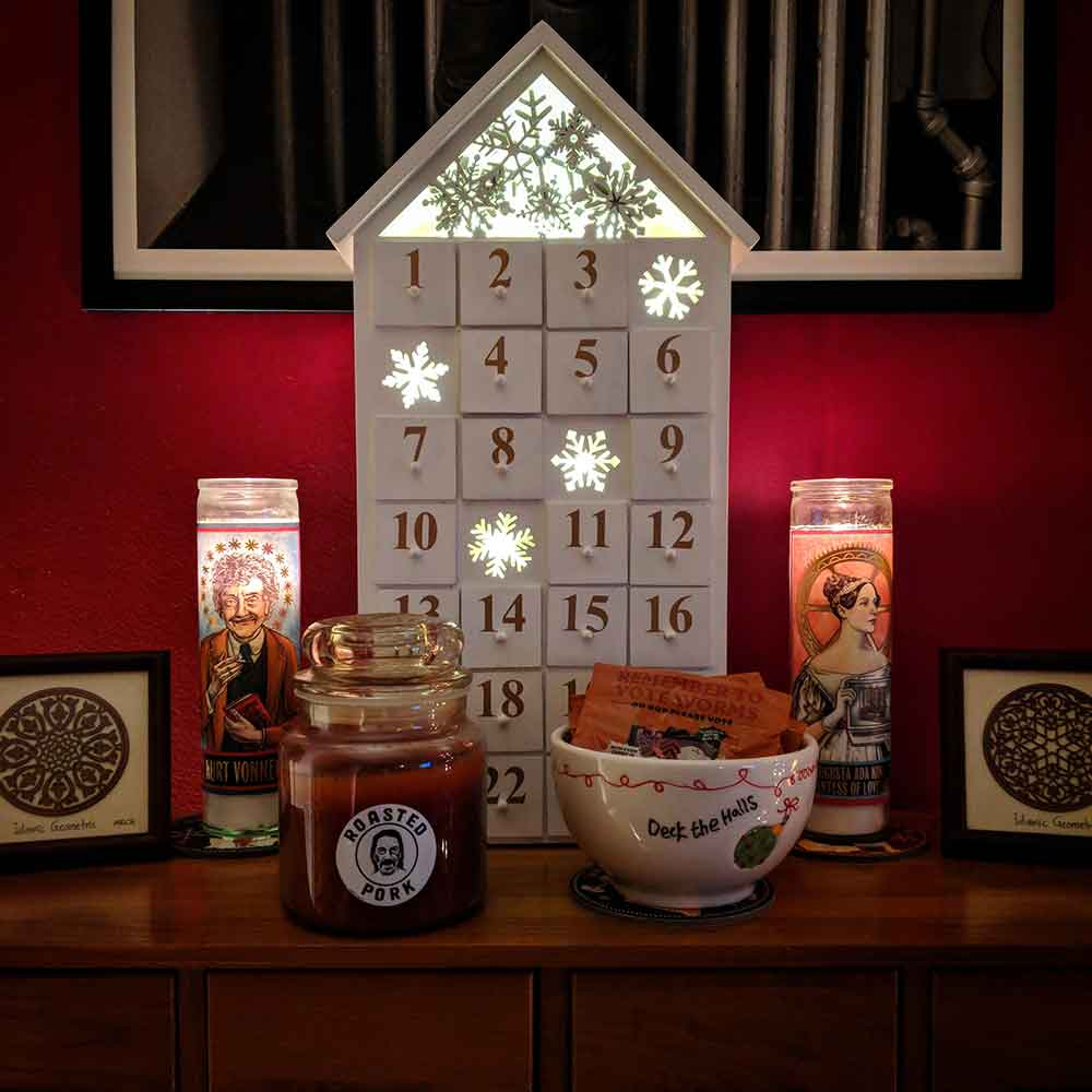 A wooden advent calendar flanked by two tall candles (one of Ada Lovelace, one of Vonnegut), and two Islamic geometric woodcuts. In the foreground is a large brown candle labeled 'roasted pork' and a bowl of gummi worms. All this on a wooden card catalog against a red wall.