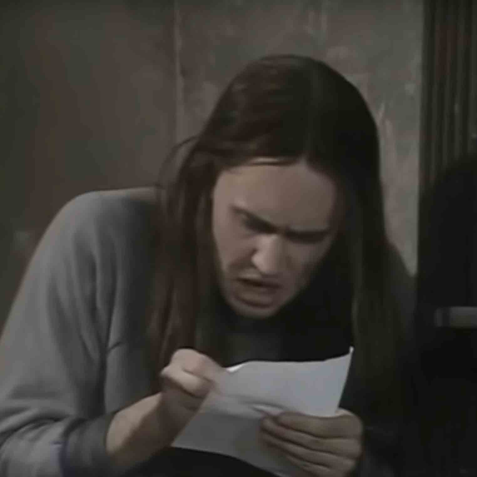 "Neil from ""The Young Ones"" writing a letter."