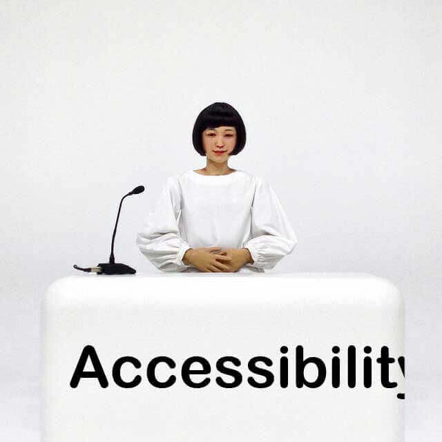 A female-appearing android dressed in white sits behind a white desk in a white room. Across the front of the desk is the word 'Accessibility', except it does not fit on the desk.