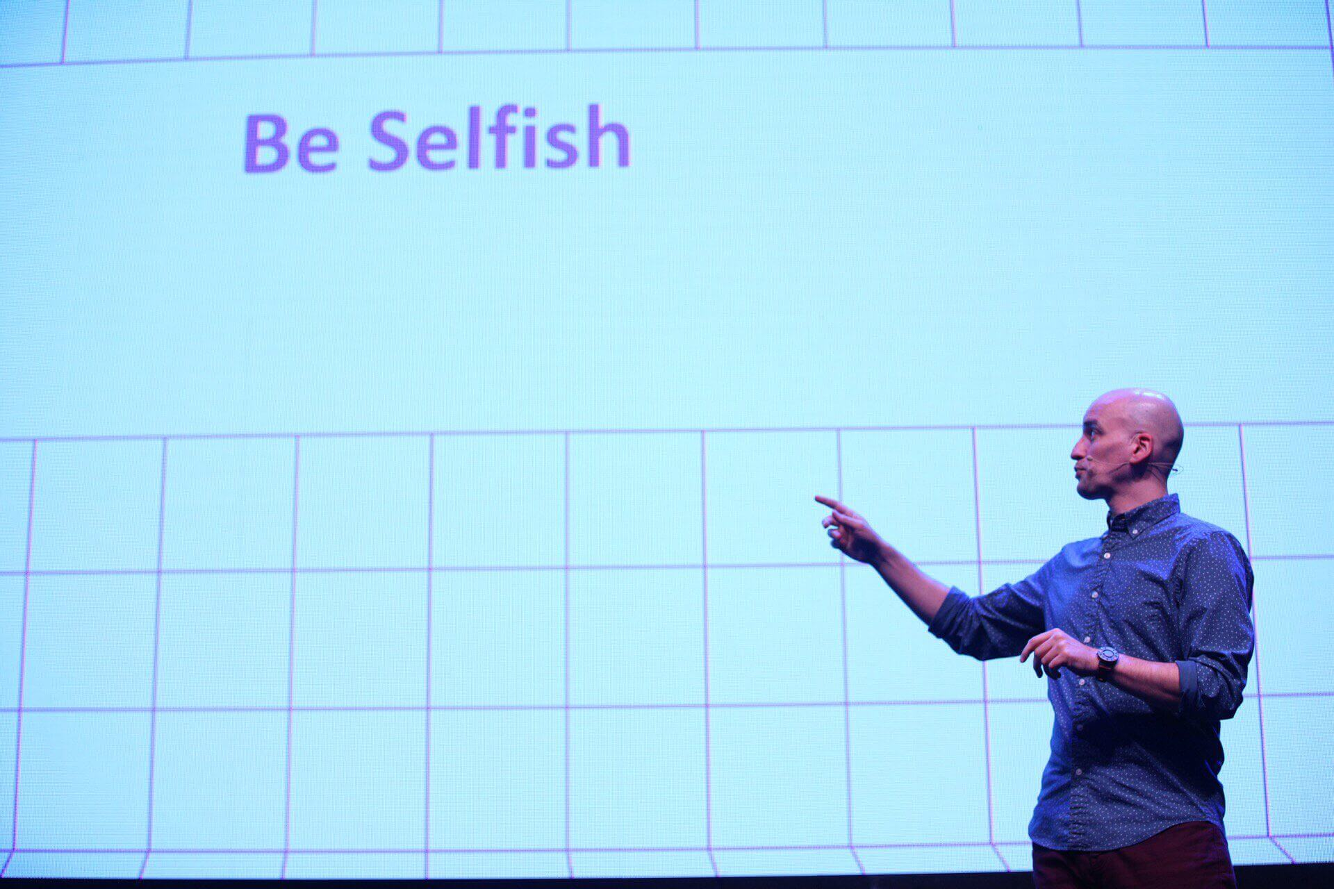 "Adrian pointing at the text ""Be selfish"" on his slide."