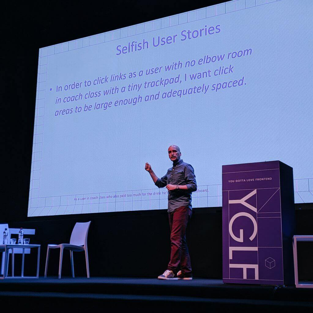 "Adrian Roselli on-stage at YGLF Lithuania. Slides read ""Selfish User Stories: In order to click links as a user with no elbow room in coach class with a tiny trackpad, I want click areas to be large enough and adequately spaced."""