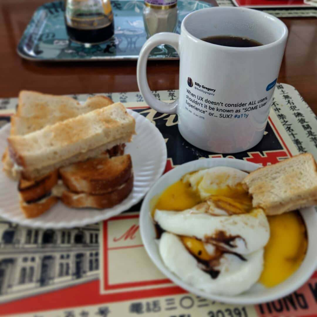 Poached eggs, soy sauce and white pepper with slices of toast slathered in kaya jam for dipping; on the mug is Billy Gregory's 2015 #SUX tweet.
