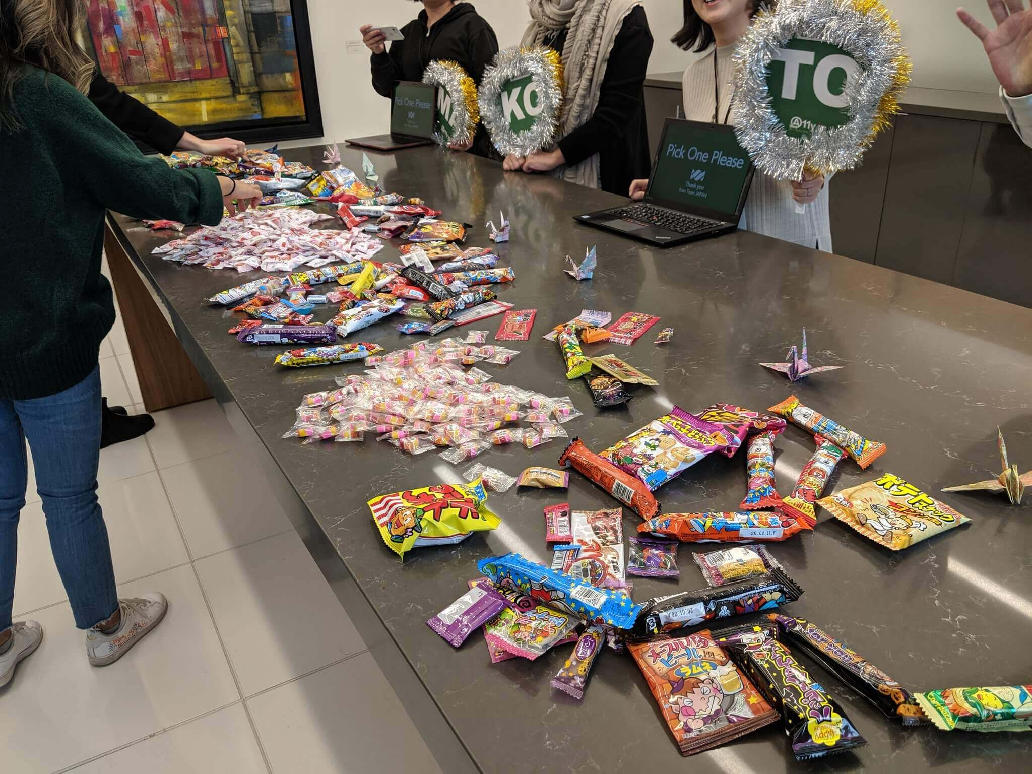 A long table covered with Japanese candies and a team from Japan standing behind it.