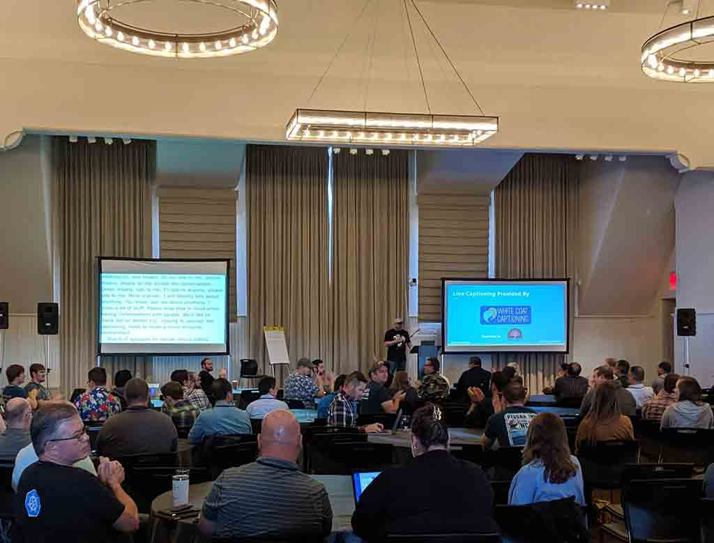 Looking across a room of about 200 people to a stage at the far end when two screens. A slide showing my name and logo, Adrian Roselli LLC, is showing a few feet away from the screen showing the captions where the organizer is thanking me for helping by sponsoring the captions.