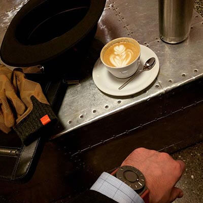 Looking down at my arm in a suit resting next to a cappuccino, watch visible below sleeve.